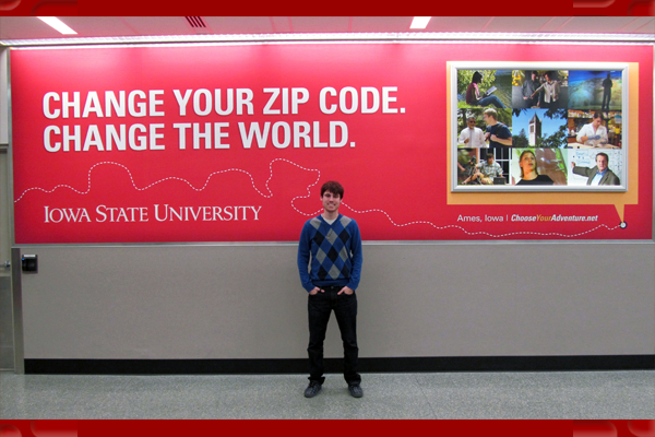 Cody Hoover stands in front of an Iowa State University sign at the Des Moines Airport, before he starts his trip to Denmark.