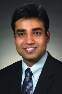 Professional headshot photo of Santosh Pandey, smiling at the camera and wearing a suit and tie