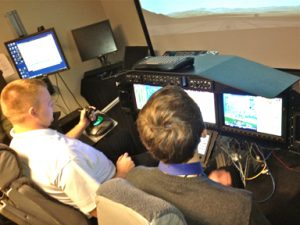 Adam Kaas and Stephen March in the flight simulator