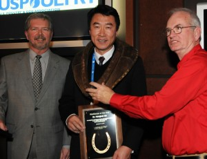 "Hongwei Xin was named the  2014 USPOULTRY Workhorse of the Year at the International Poultry Expo, part of the International Production & Processing Expo. He was ""collared"" with an actual horse collar by Dr. Charlie Olentine (right), 2013 Workhorse of the Year recipient. Xin was presented with a commemorative plaque by 2013 USPOULTRY chairman, James Adams (left), Wenger Feeds, Rheems, PA."