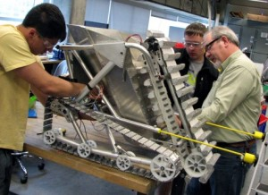 Members of Cyclone Space Mining assemble the team's robot during a recent workday in a campus lab. Left to right are Robert Prucha, a sophomore from Missouri Valley; Brandon Keesling, a sophomore from Oskaloosa; and Jim Heise, the team's faculty adviser. Photo by Mike Krapfl.