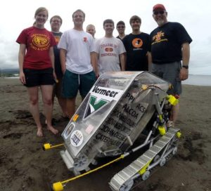 Members of Cyclone Space Mining, left to right, Katie Goebel, John Heinig, Brian Jend, Nathan Beougher, David Peiffer, Phil Molnar, Alex Grant, and Faculty Adviser Jim Heise demonstrate their robotic miner on Hilo Bay Beach in Hawaii. Photo by Pacific International Space Center for Exploration Systems.