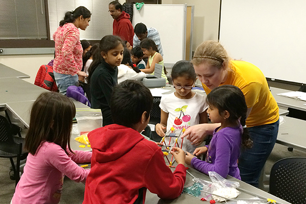 Civil engineering sophomore Paige Taylor helps a few Story County elementary school students build a K'Nex bridge on Feb. 8, 2015.