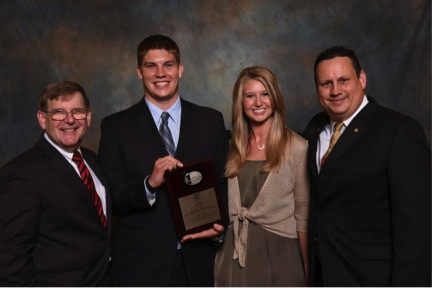 Kirpes (center-left) pictured holding the IIE Outstanding Early Career in Business/Industry Award with his wife, Nicole Basile (center right), the president of IIE, James Moore (far left), and the president-elect of IIE, Michael Foss (far right).