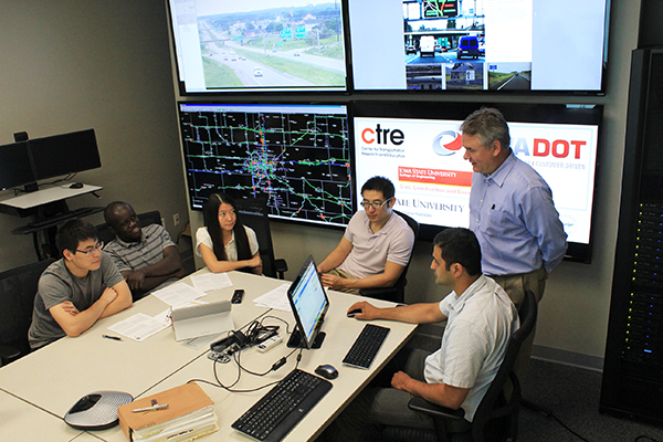Faculty and student researchers analyze Iowa highway traffic data, in real time, at the Iowa State University Traffic Operations Laboratory. Pictured, from left, are doctoral student Chenhui Liu, postdoc research associate Yaw Adu-Gyamfi, doctoral student Tingting Huang, doctoral student Shuo Wang, Associate Professor Anuj Sharma, and Neal Hawkins, director of the Center for Transportation Research and Education at Iowa State.