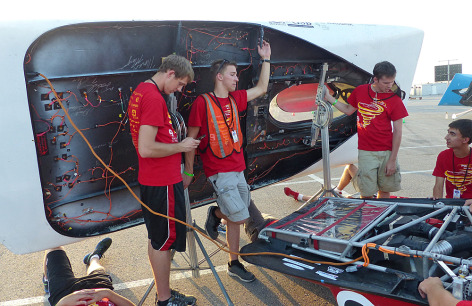 Members of Team PrISUm tilt their car's solar array to the sun for better charging. Once the day's solar racing is done, competing teams have several hours to recharge their cars' battery packs. Photo by the Formula Sun Grand Prix.