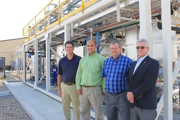Eric Cochran (second from left), associate professor of chemical and biological engineering, and Chris Williams (second from right), Gerald and Audrey Olson Professor of civil, construction and environmental engineering, led Iowa State's research efforts in building a pilot-scale bio-polymer plant at the university's BioCentury Research Farm. Here they pose at the facility's dedication August 26, 2015.
