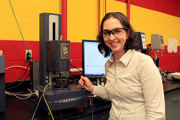 Ashley Buss, assistant professor of civil, construction and environmental engineering, demonstrates a rheology test of an asphalt binder in the Advanced Asphalt Materials Laboratory in Town Engineering Building.