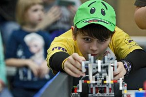 A student lines up a robot during FIRST LEGO® League Competition. (Photo by Iowa State Engineering Kids)