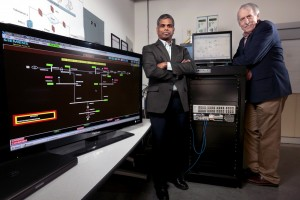 "Manimaran Govindarasu and Doug Jacobson, left to right, are leading studies of power grid cyber security, including development of the ""PowerCyber"" testbed. (Photo by Christopher Gannon)"