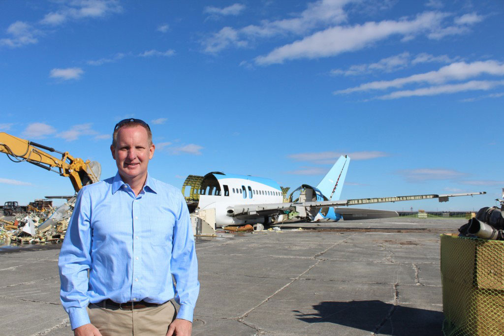 Christensen in front of the 757 ecoDemonstrator being dismantled during the aircraft recycling process.