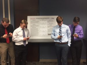 Bohle (far left) and his research team, with cell phones in hand, at the CCEE Freshman Research Initiative Poster Session (photo courtesy Peter Savolainen)