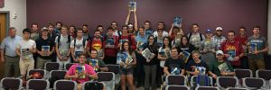 Students in CE 382 hold their books high after class with instructors Chris Williams and Ashley Buss. <i>(Photo by Kate Tindall).</i>