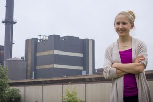 Kristen Cetin stands in front of the Iowa State University Power Plant. Her research on energy production would impact facilities like this one during times of peak usage. <i> Photo by Kate Tindall. </i>