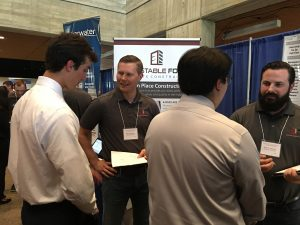 Eric Lindquist <i>(center left)</i> speaks to an engineering student during the career fair.