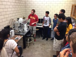 Kyle Miller, MSE graduate student, shows students lab equipment.