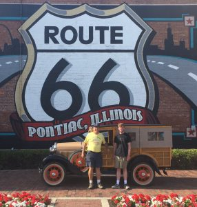 Christopher Gillis and Dr. T. Lindsay Baker stand in front of a mural painted outside of the Route 66 Association Hall of Fame and Museum in Pontiac, Illinois.