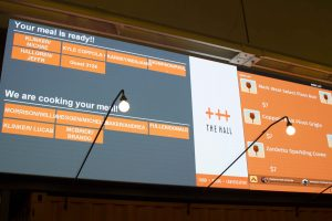 Large screens displaying wait times and ready orders are one way The Hall has sped up the food serving process.