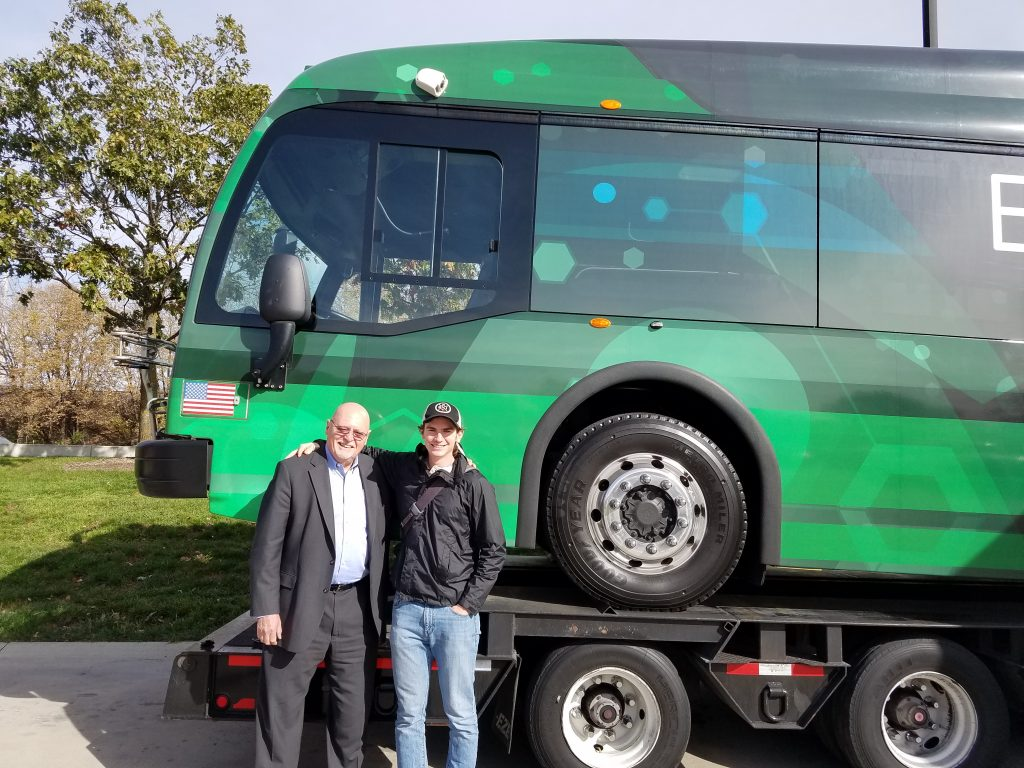 Mechanical engineering senior Ryan Saunders poses with Proterra founder Dale Hill in front of a Proterra electric bus