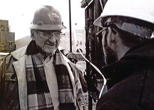 Nat Fox discusses work with a fellow engineer on a construction site. <i>Photo courtesy Dick Handy.</i>