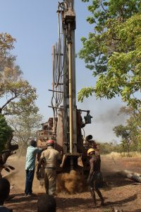 A local contractor drills a borehole for a mechanized well.