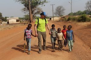 Kevin Prince (middle, in yellow shirt) walks with children in Ullo. EWB members spend time getting to know the community members while working on water distribution centers. <i> Photos courtesy Kevin Prince.</i>