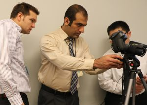 Arabzadeh <i>(center)</i> demonstrates research techniques at PEGASAS' annual meeting. <i> Photos courtesy Arabzadeh. </i>