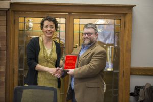 Student Adviser and Lecturer Virginia Hanson presents Freeman with a plaque for his years of service to the faculty senate. (Christopher Gannon/Iowa State University)