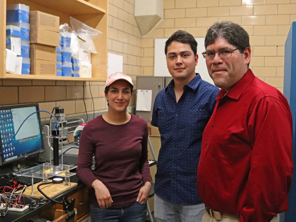 A faculty member, grad student and undergrad student stand together in a lab next to a instrument they built together.