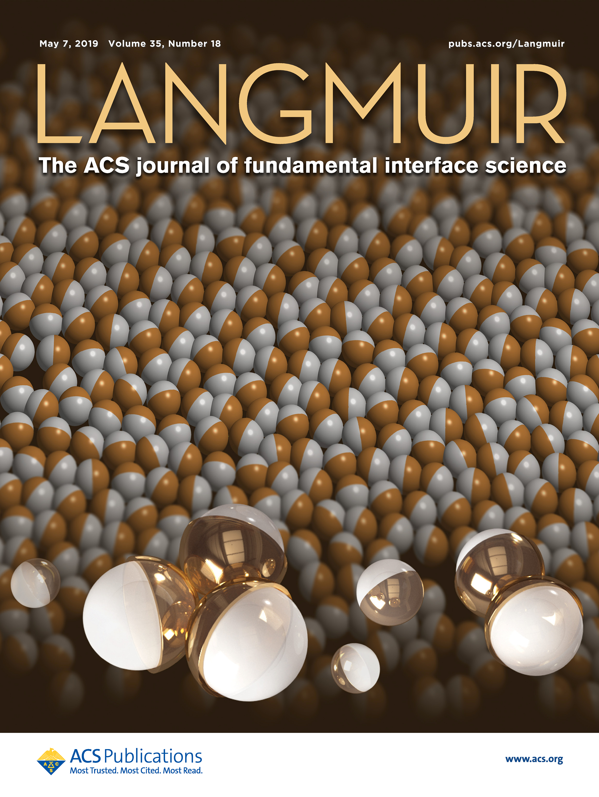 Cover of academic journal showing a layer of gold and white spheres.