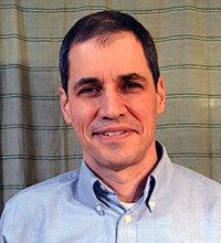 A smiling man wearing a light blue, button-down shirt