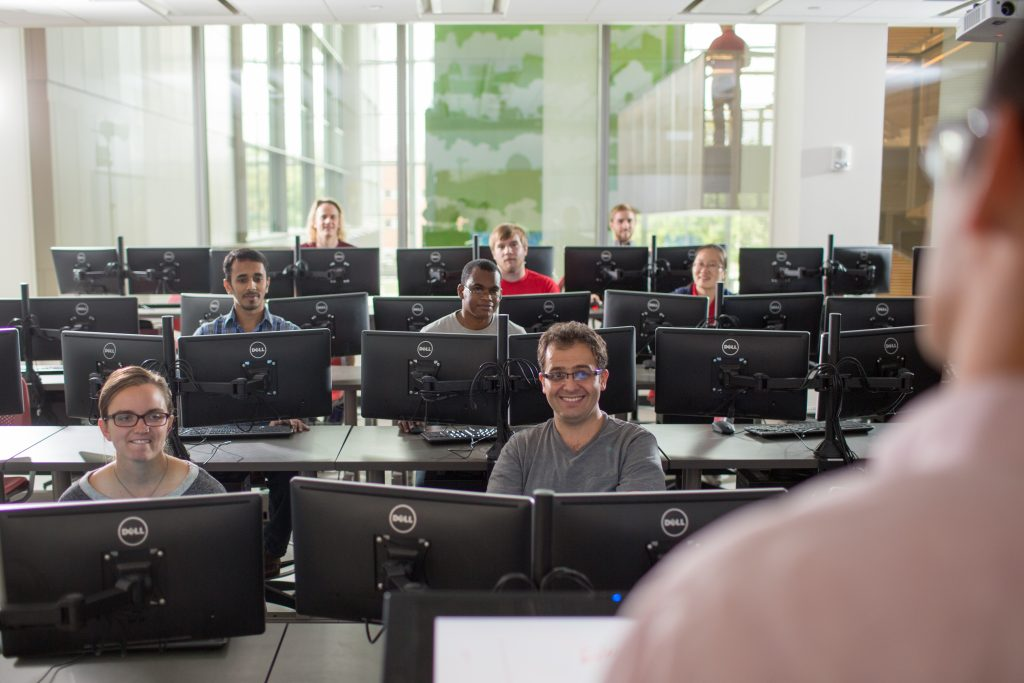 An instructor faces a room full of students in a computer lab classroom