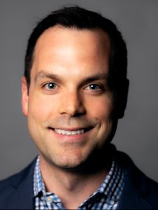 Headshot of Michael Anctil on a gray background.
