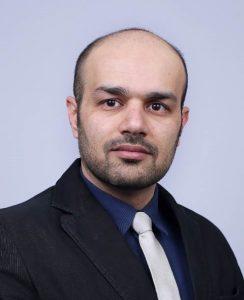 Headshot of Mohammad Tayeb Al Qaseer on a gray background.