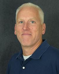 Headshot of Steve Zoz on a dark gray background.