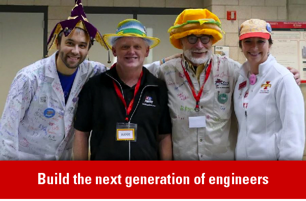 Members of the volunteer team and judges for First and Lego League stand together wearing costume hats