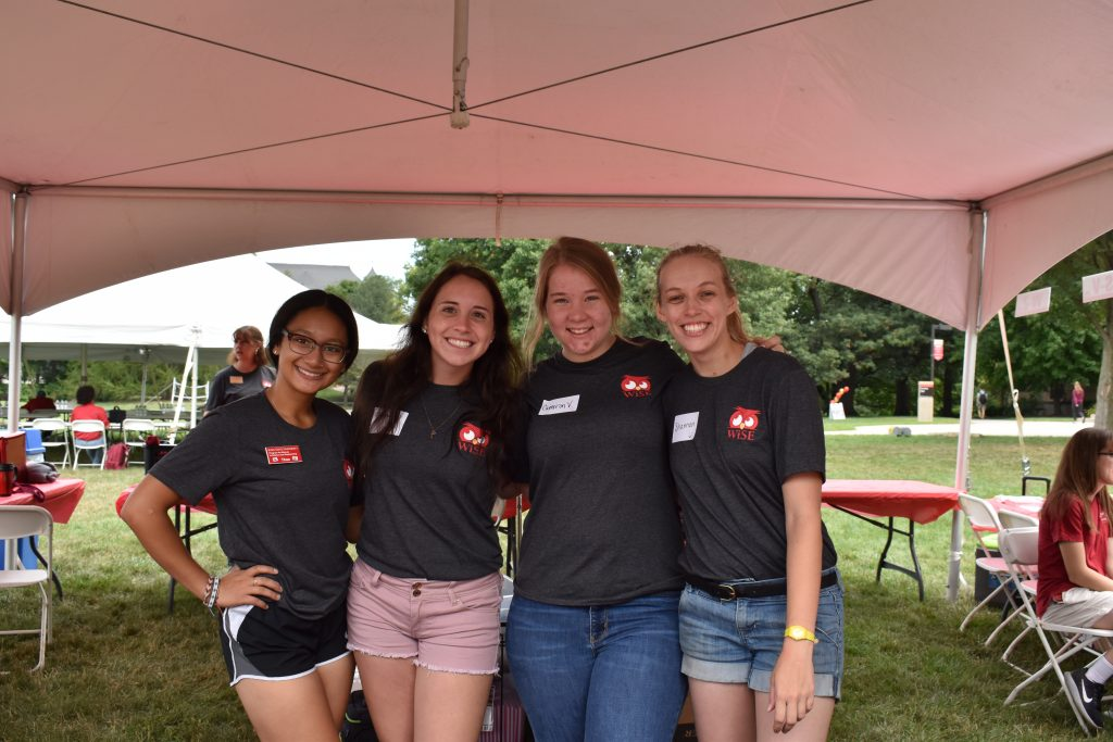 Four female college students stand in a white tent near picnic tables