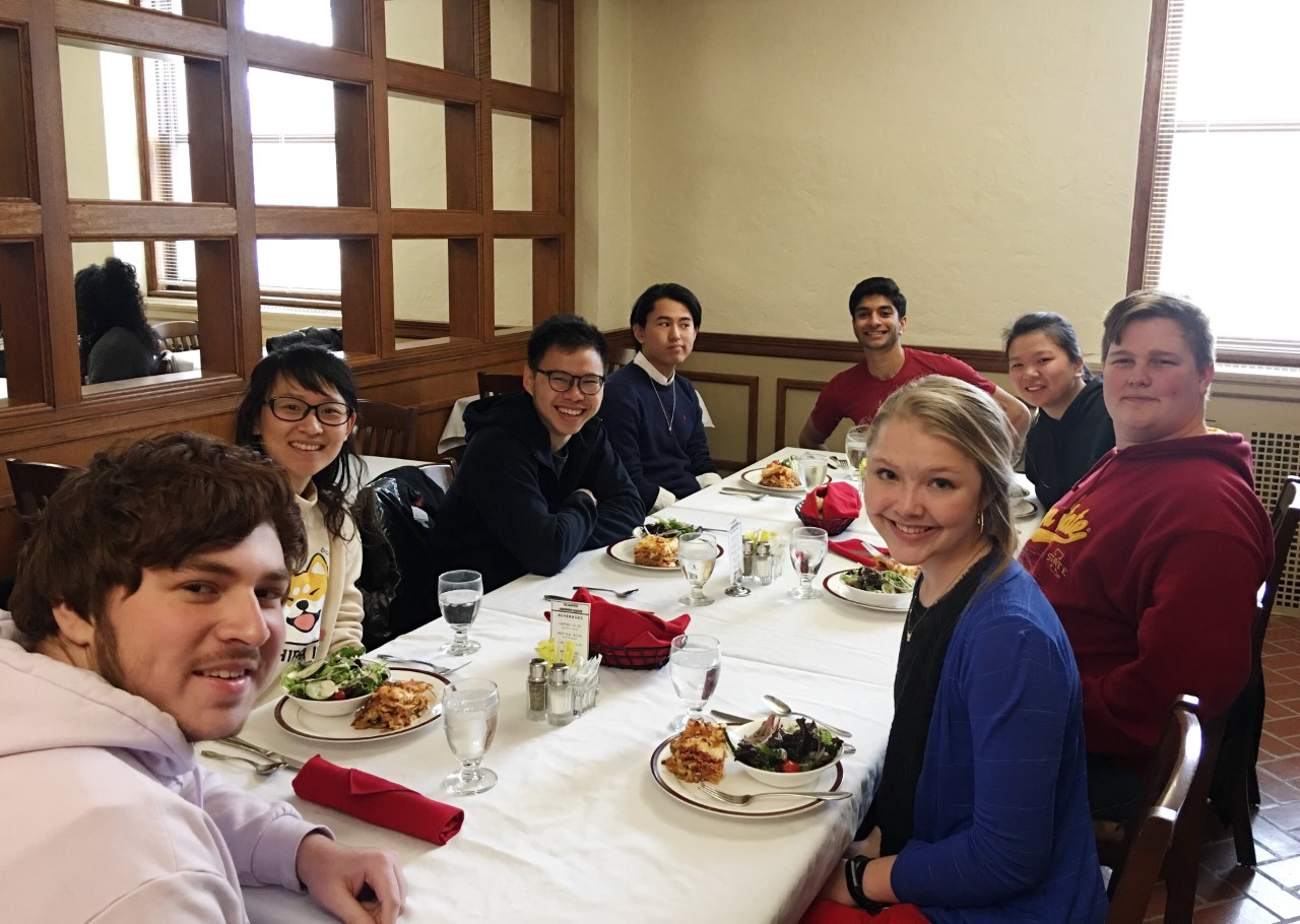 Students are seated at a table eating lunch and looking toward the camera