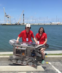 Two students stand in front of an ocean bay and pose behind a space mining robot they helped build