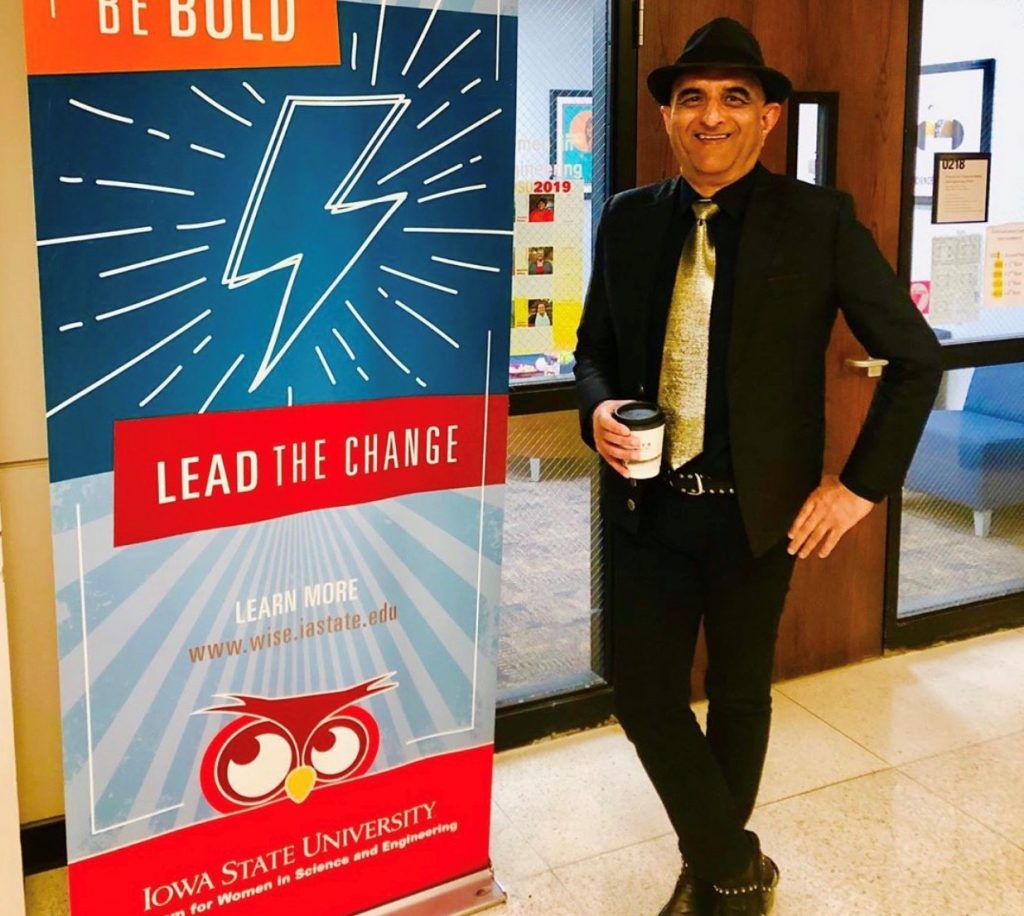 Man wearing a fedora hat and gold tie holds coffee in front of an office entrance