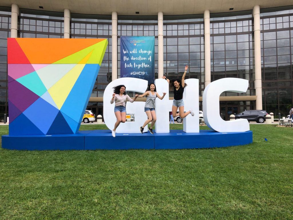 Three female college students are jumping mid-air in front of an outdoor sign with block letters