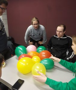 Students collaborating on balloon activity with peer mentor Dominique Serrano