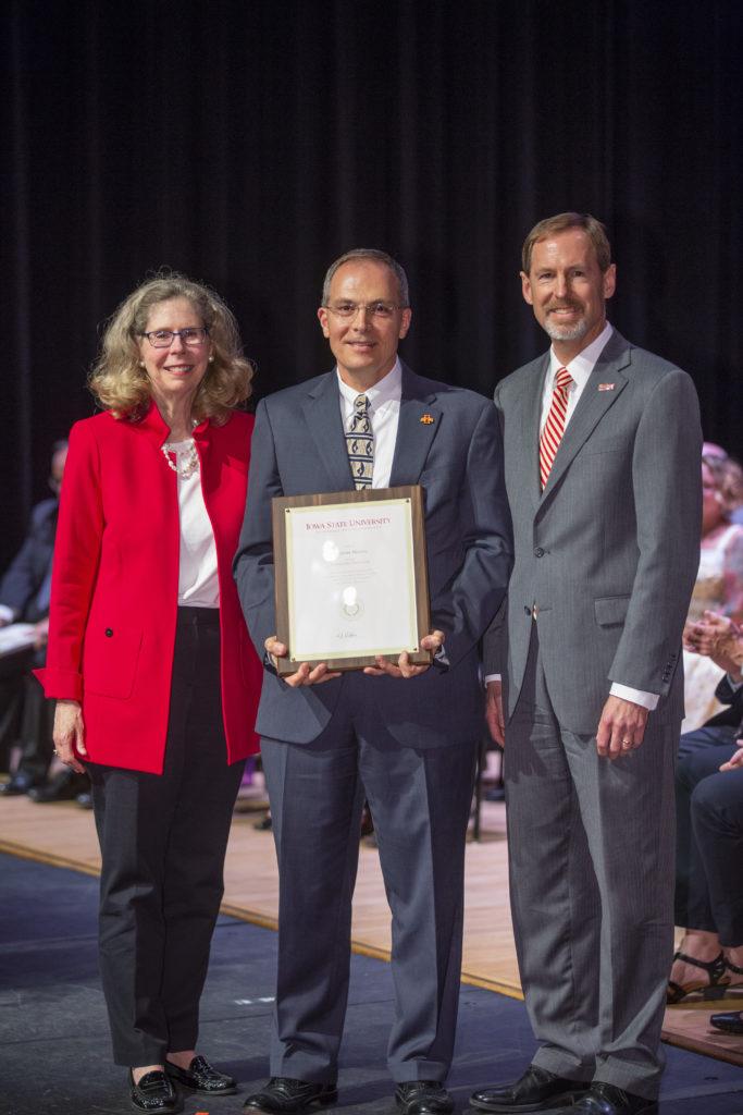 Ted Heindel holds a framed award alongside university leaders