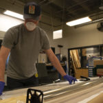 Craig measures out a piece of clear plastic, before cutting it with a box cutter.