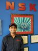 Shubham poses in front of a framed photo of a ball bearing. The red letter for NSF are seen at the top of the shot. Shubham is smiling and wearing a work shirt with the NSK logo.