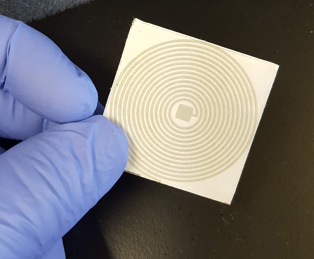 Gloved hand holds a square sensor with concentric circles on its surface