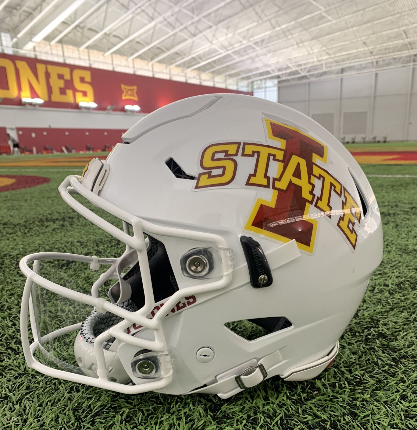 A white football helmet with the I-State athletic logo in red and yellow on the side