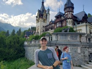 Former student poses with a castle, greenery and mountains in the back. Photo take in Romania