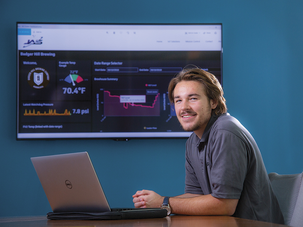 Dillon Jensen poses with the Jensen Applied Sciences interface on a screen in the background