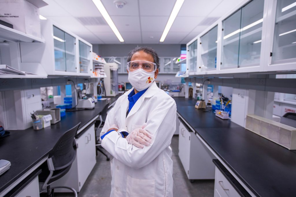 Scientist stands in a lab, wearing a white lab coat, gloves and a white face covering.